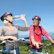 Senior couple drinking water during bike ride — Stock Photo