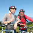 Senior couple drinking water during bike ride - Stock Photo