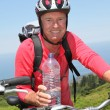 Cheerful senior man on mountain bike ride — Stock Photo #18212143