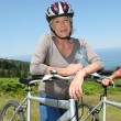 Portrait of happy senior woman on mountain bike — Stock Photo