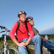 Senior couple riding mountain bikes in natural landscape — Stock Photo #18212153