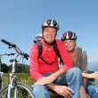 Senior couple riding mountain bikes in natural landscape — Stock Photo