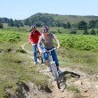 Senior couple riding mountain bikes in natural landscape — Stock Photo #18212175