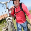 Senior man carrying mountain bike - Stock Photo