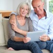 Senior couple using electronic tablet at home — Stock Photo #18213021