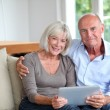 Senior couple using electronic tablet at home — Stock Photo #18213061