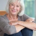 Portrait of smiling senior woman sitting in sofa — Stock Photo