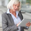Businesswoman using electronic tablet outside airport — Stock Photo #18213185