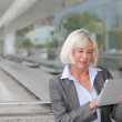 Businesswoman using electronic tablet outside airport — Stock Photo