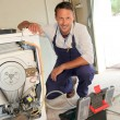 Foto de Stock  : Plumber fixing washing machine