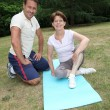 Stock Photo: Sports coach training senior woman with stretching exercises
