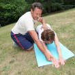 Stock Photo: Sports coach training senior womwith stretching exercises
