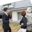 Real-estate agent with senior couple buying new house - Stock Photo