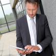 Stock Photo: Businessmusing electronic tablet outside offices building