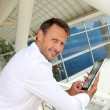 Businessman using electronic tablet outside the airport — Stock Photo