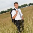 Businessman standing in wheat field — Stock Photo