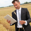 Businessman with electronic tablet standing in wheat field — Stock Photo