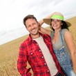 Happy couple standing in wheat field — Stock Photo
