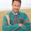 Portrait of happy farmer in wheat field — Stock Photo