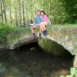 Couple sitting on a bridge in forest — Stock Photo
