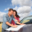 Couple looking at road map on car hood — Stock Photo #18214805