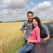 Stock fotografie: Couple standing by convertible car
