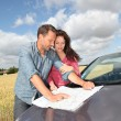 Couple looking at road map on car hood  — Stock Photo