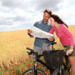 Royalty-Free Stock Photo: Couple riding looking at map on bike ride