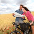Couple riding looking at map on bike ride — Stock Photo