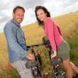 Smiling couple riding bicycle in country field - Stock Photo
