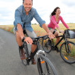 Couple riding bicycle on country road - Stock Photo