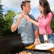 Happy couple cooking meat on barbecue grill — Stock fotografie #18214931