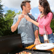 Happy couple cooking meat on barbecue grill — Stockfoto