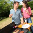 Happy couple cooking meat on barbecue grill — Stockfoto #18214933