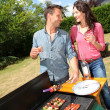 Happy couple cooking meat on barbecue grill — Stock Photo #18214933