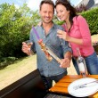 Happy couple cooking meat on barbecue grill — Stock fotografie