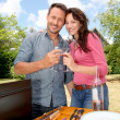 Foto de Stock  : Happy couple cooking meat on barbecue grill