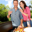 Foto Stock: Happy couple cooking meat on barbecue grill