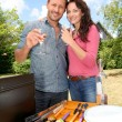 Happy couple cooking meat on barbecue grill — Stock fotografie #18214947