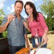 Happy couple cooking meat on barbecue grill — 图库照片
