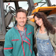 Farming couple standing by tractor  — Stock Photo