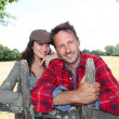 Couple leaning on fence in country field - Stock Photo