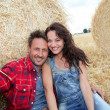 Couple relaxing in hay bales — Stock Photo