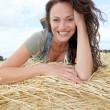 Beautiful woman laying down bale — Stock Photo