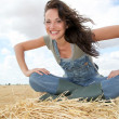 Woman having fun sitting on hay bale — Stock Photo