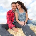 Happy couple sitting on bale in farmland — Stock Photo