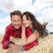 Happy couple sitting on bale in farmland — Stock Photo