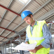 Engineer checking plan in building under construction — Stock Photo #18217009