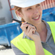 Stock Photo: Womusing walkie-talkie on construction site