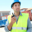 Stock Photo: Foremusing walkie-talkie on construction site